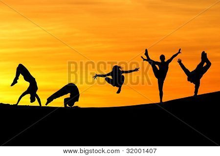 silhouette of female gymnasts in sunset