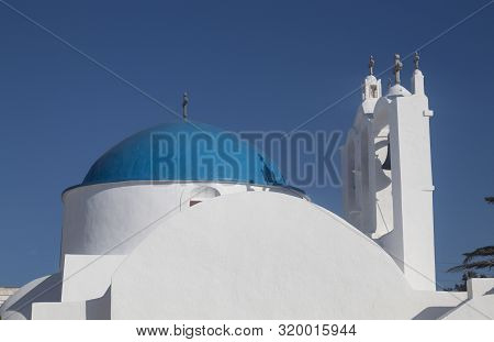 Greece, The Island Of Sikinos.  The Village Square. A View Of The Main Church.  Clear Blue Sky. Brig