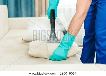 An Employee Of A Cleaning Company Provides A Chemical And Steam Cleaning Service For The Sofa. Steam