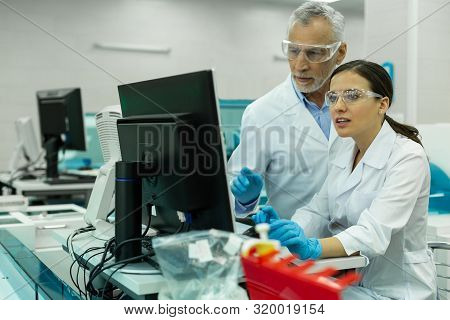 Cheerful Brunette Woman Standing In Front Of Computer