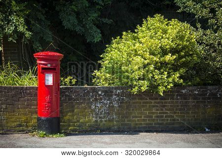 British Red Postbox In Rural Street On Sunny Day