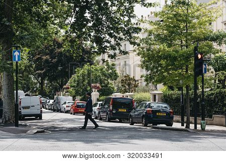 London, Uk - July 18, 2019: Parking Warden Crossing The Road In Marylebone, A Chic Residential Area