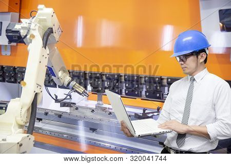 The Engineer Programming The Robotic Arms For Loading The Sheet Metal To The Hydraulic Bending Machi