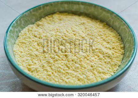 Dry Organic Corn Meal Flour In Ceramic Bowl.