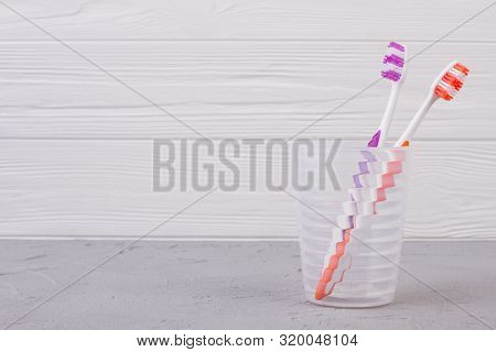 Colorful Toothbrushes In Glass On Wooden Background. Two Toothbrushes In Glass. Space For Text. Dent