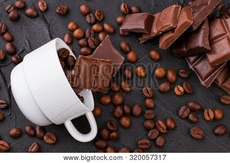 Cup With Coffee Beans And Chocolate On Dark Background. Background Of Chocolate Bars, Coffee Cup And
