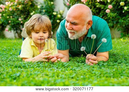 Men Generation. Happy Child With Grandfather Playing Outdoors. Child With Grandfather Dreams In Summ