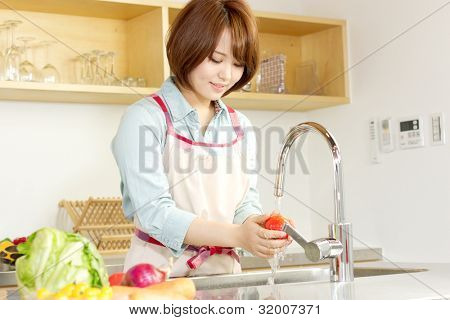 Beautiful young woman in kitchen making salad. Portrait of asian woman.