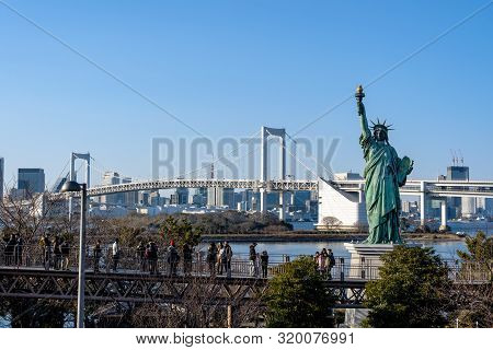 Tokyo, Japan - Feb 2019 : Undefined Tourist Seesighting On The Bridge With Statue Of Liberty And Rai