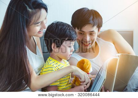 Happy Asian Family. Cute Little Boy Or Son Learning To Read Some Letters. Mother And Father Teaching