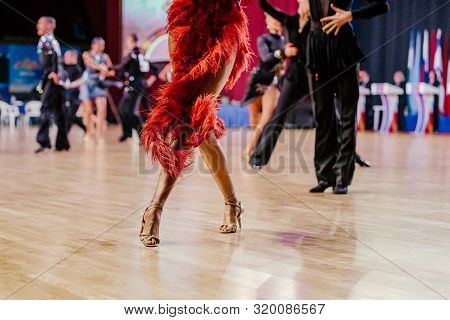feet woman dancer in red dress with fringe dancing latino program poster