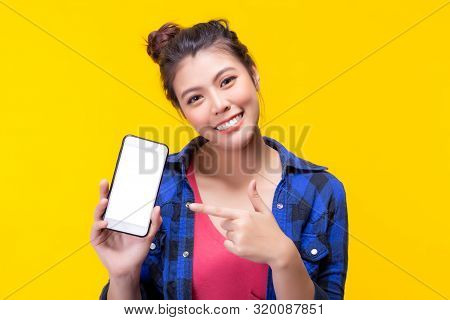 Pretty Asian Woman Holding Smartphone And Pointing Finger To The Smartphone. Attractive Beautiful Yo