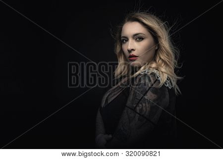 Fashion portrait of young woman blonde in transparent evening dress. Blowing hair, professional makeup with red lips. Beauty of elegant plus size model. Stylish shot with copy space. Black background.