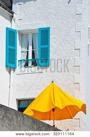 Sunny View Of A White House With A Blue Window With Shutters And An Orange Parasol