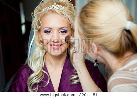 The beautiful bride during make-up at visagiste in the morning before wedding poster