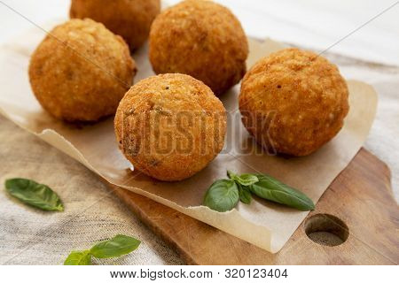 Homemade Fried Arancini With Basil On A Rustic Wooden Board, Side View. Italian Rice Balls. Close-up