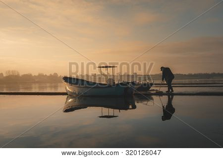 Hornsea, Uk - 20th Janurary 2019: The Caretaker Of The Mere Washes The Ice Away From The Decking On