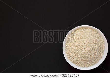 Organic Arborio Rice In A White Bowl On A Black Surface, Top View. Flat Lay, Overhead, From Above. C