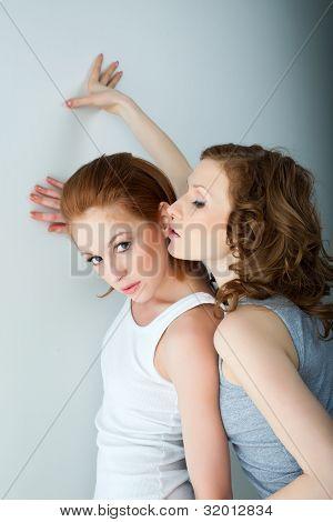 Two beauty woman in tank top near wall