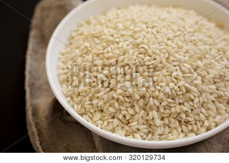Organic Arborio Rice In A White Bowl, Low Angle View. Close-up.
