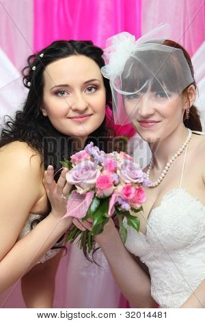 two young brides wearing white dresses hold beautiful bouquet of roses; Focus on women on left