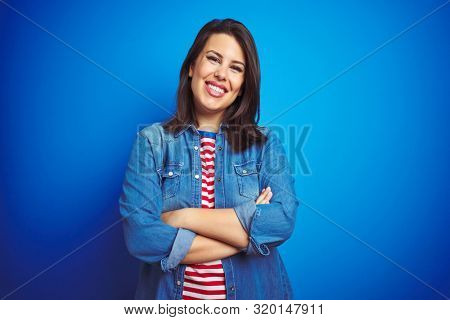 Young beautiful brunette woman wearing casual blue denim jacket over blue isolated background happy face smiling with crossed arms looking at the camera. Positive person.