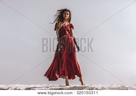 Beautiful Young Fashionable Woman In Elegant Dress At The Beach At Sunset