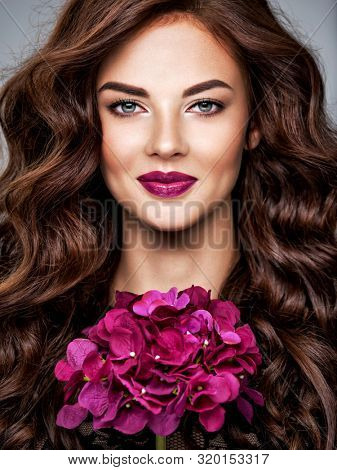 Beautiful woman with long curly hair and bright purple make-up.  Young caucasian gorgeous adult girl with easy smile on face. Model. Closeup woman's portrait. Vivid make-up. Sexy female. Violet lips.