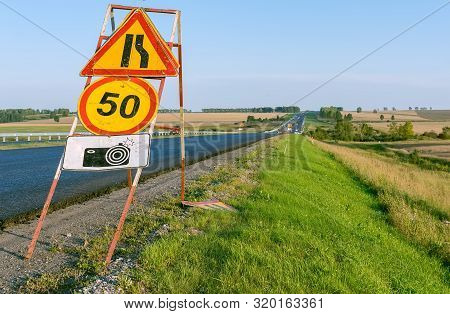 road sign road repair, speed limits and warnings about the camera fixing violations on the background of a country highway in the autumn poster