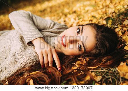 A portrait of a beautiful young woman lying on the ground with golden autumn leaves. Lifestyle, autumn fashion, beauty.