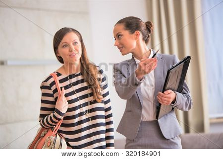 Confident young saleswoman gesturing to female client while holding document in apartment