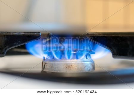 Old White Kitchen Stove Cook With Blue Flames Burning. Household Gas Stove. Can Be A Source Of Fire