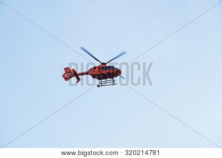 Rescue Helicopter Or Air Ambulance - Red Air Medical Services Heli Copter Midair Against Blue Sky