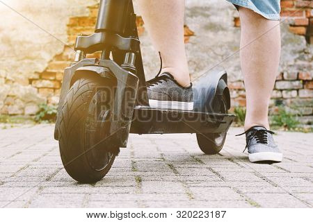 Legs Of Unrecognizable Person With Electric Kick Scooter Or E-scooter - E-mobility Or Micro-mobility