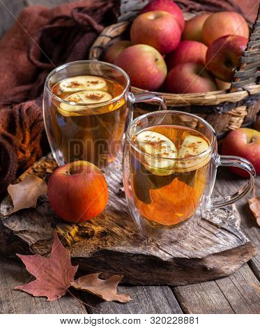 Two Cups Of Apple Cider With Apple Slices Sprinkled With Cinnamon On A Rustic Wooden Surface And Bas
