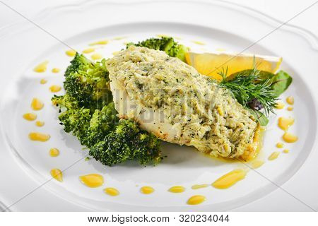 Macro shot of pike perch or zander fillet in cream sauce with broccoli isolated. Restaurant main course with fried sander fish or pike meat with lemon and greens closeup poster