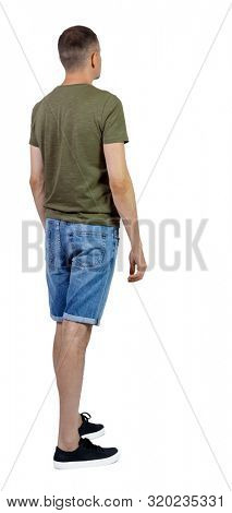 Back view of young manin shorts looking. Rear view people collection. backside view of person. Isolated over white background. The guy in the sneakers looks sideways ..