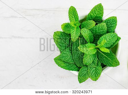 Peppermint Leaves On White Wooden  Background. Bunch Of Mint, Spearmint Leaves. Top View. Copyspace