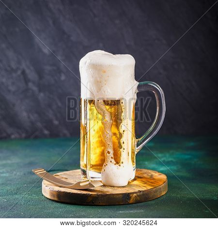 Glass Mug With Beer With Foam And Water Drops On A Dark Green Background