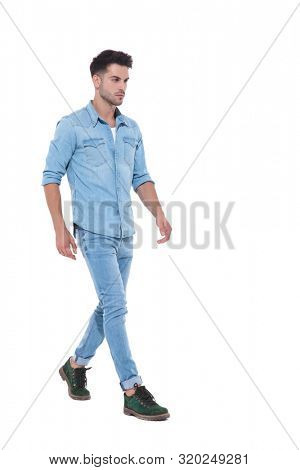 sideview of a powerful and confident man walking, wearing denim, standing isolated on white background, full body, full length