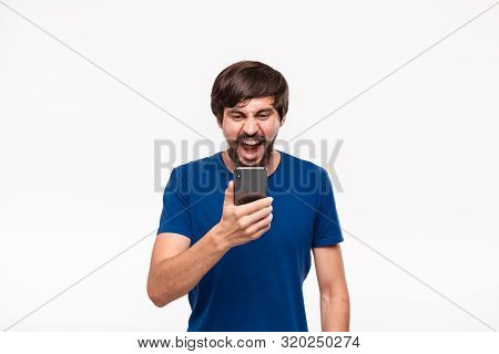 Displeased Handsome Brunet Man In A Blue Shirt With Beard And Mostaches Shocked Looking At The Scree