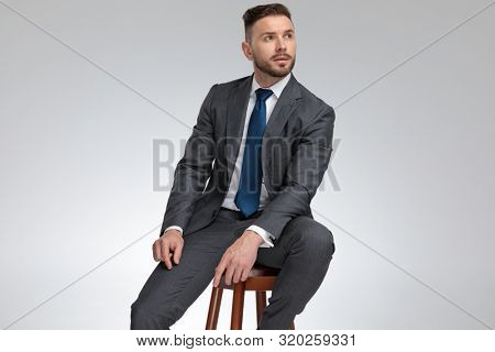 young elegant businessmn sits on stool and dreams, looking up at something on grey background