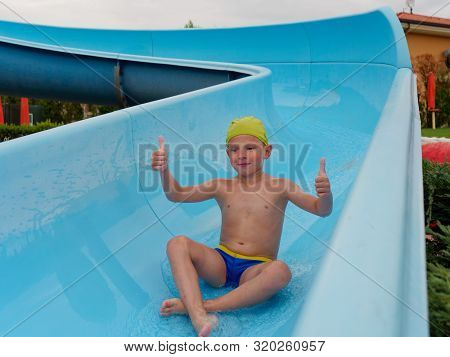 Boy Rides Water Slide Rides At The Water Park