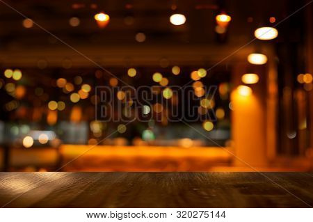 Top Of Wood Table With Bokeh Of Glor Blur Lamp Light In Party Bar Or Pub In The Christmas Dark Night