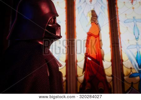 AUG 31 2019: Recreation of a scene from the Star Wars Battlefront II video game with Darth Vader / Anakin Skywalker viewing a stained glass memorial to his wife Padme Amidala  - Hasbro action figure