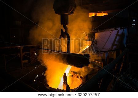 Molten steel pouring. Liquid hot metal of steel spills out of the ladle at steel factory. poster