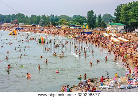 Anapa, Russia - July 26, 2008: Crowds Of People Relaxing On Sandy Beach And Bathing In Sea Water In