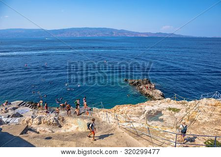 Hydra, Greece - 16 August 2019: Beach Spilia With Bar. Beautiful Greek Landscape Of Harbour Hydra To