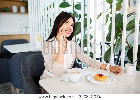 people, leisure and inspiration concept - happy asian woman with coffee, dessert and notebook daydreaming at cafe