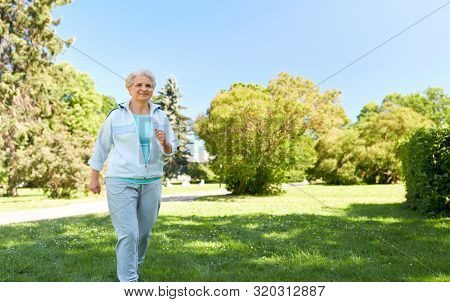 fitness, sport and healthy lifestyle concept - senior woman running or walking along summer park